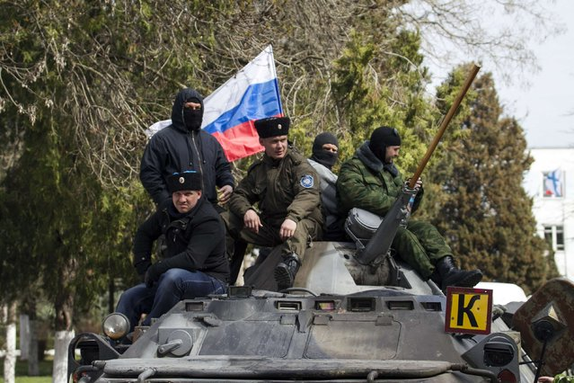 Pro-Russian supporters sit on top of a Ukrainian APC after breaking into the territory of the naval headquarters in Sevastopol, March 19, 2014. (Photo by Baz Ratner/Reuters)