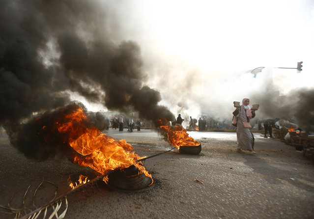 A Sudanese protester walks past burning tyres as military forces tried to disperse the sit-in outside Khartoum's army headquarters on June 3, 2019. At least two people were killed Monday as Sudan's military council tried to break up a sit-in outside Khartoum's army headquarters, a doctors' committee said as gunfire was heard from the protest site. (Photo by Ashraf Shazly/AFP Photo)