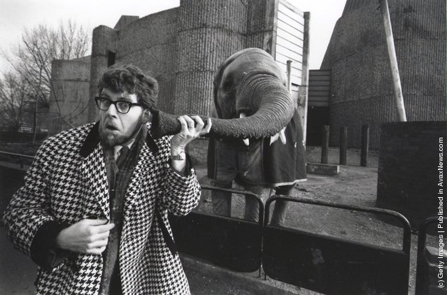 1967: Rolf Harris puts his ear to an elephant's trunk at London Zoo