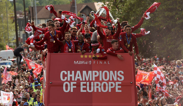 Liverpool's Spanish defender Alberto Moreno (3R) holds aloft the European Champion Clubs' Cup trophy as he stand with teammates (LtoR) Liverpool's English midfielder James Milner, Liverpool's Scottish defender Andrew Robertson, Liverpool's English midfielder Jordan Henderson, Liverpool's English midfielder Alex Oxlade-Chamberlain, Liverpool's Dutch midfielder Georginio Wijnaldum, Liverpool's English striker Daniel Sturridge and Liverpool's English defender Trent Alexander-Arnold during an open-top bus parade around Liverpool, north-west England on June 2, 2019, after winning the UEFA Champions League final football match between Liverpool and Tottenham. Liverpool's celebrations stretched long into the night after they became six-time European champions with goals from Mohamed Salah and Divock Origi to beat Tottenham – and the party was set to move to England on Sunday where tens of thousands of fans awaited the team's return. The 2-0 win in the sweltering Metropolitano Stadium delivered a first trophy in seven years for Liverpool, and – finally – a first win in seven finals for coach Jurgen Klopp. (Photo by Oli Scarff/AFP Photo)