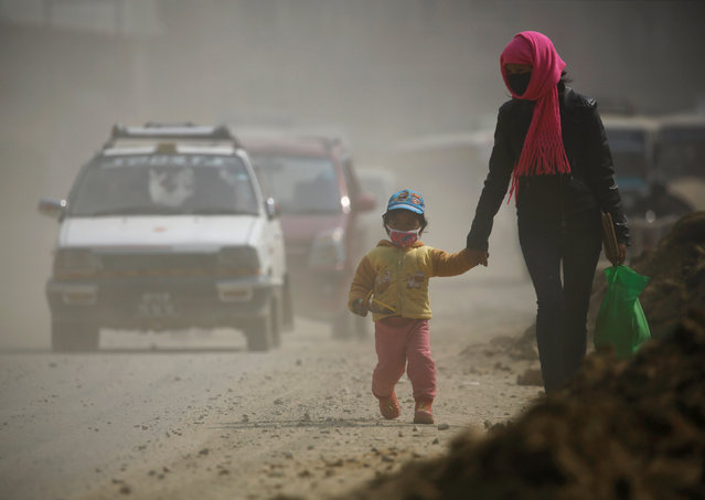 A woman and her child wearing masks walk along a dusty road in Kathmandu, Nepal February 27, 2017. (Photo by Navesh Chitrakar/Reuters)