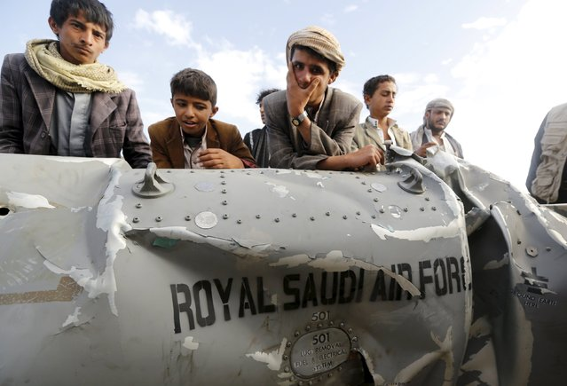 People stand by part of a Saudi fighter jet found in Bani Harith district north of Yemen's capital Sanaa May 24, 2015. (Photo by Khaled Abdullah/Reuters)