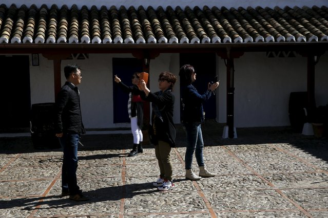 Tourists take pictures at the inn where locals believe Don Quixote might have been knighted in Puerto Lapice, Spain, April 8, 2016. (Photo by Susana Vera/Reuters)