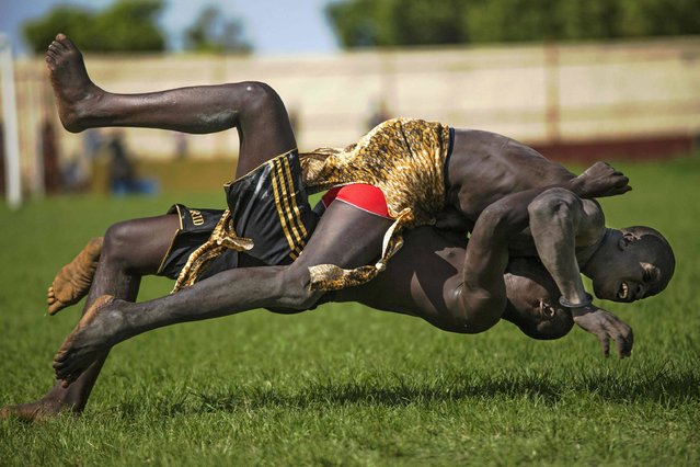 "Two participants from Imatong and Terekeka counties take part of the South Sudan National Wrestling Competition for peace at Juba Stadium, on April 20, 2016. South Sudan is holding a ""wrestling for peace"" tournament, bringing together athletes from around the country. The last big tournament was canceled when civil war broke out in December 2013. (Photo by Albert Gonzalez Farran/AFP Photo)"