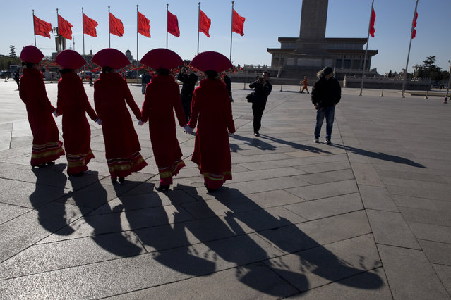 In this photo taken Sunday, March 12, 2017, hospitality staff wearing ethnic minority costumes pose for photos near the Great Hall of the People where a plenary session of the National People's Congress is held in Beijing, China. (Photo by Ng Han Guan/AP Photo)