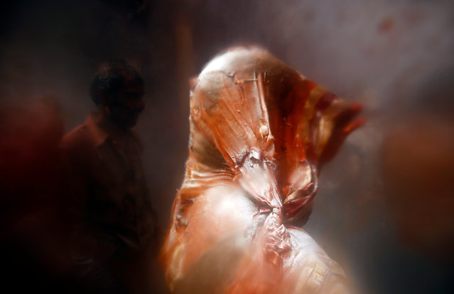 """A woman holds her veil as she takes part in """"Huranga"""", a game played between men and women a day after Holi, at Dauji temple near the northern city of Mathura, India March 14, 2017. (Photo by Adnan Abidi/Reuters)"""