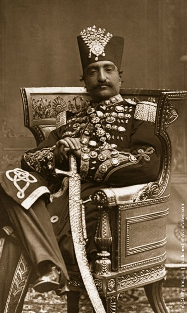 1880: Nasiruddin, Shah of Persia (Iran) in regal attire, with his scimitar