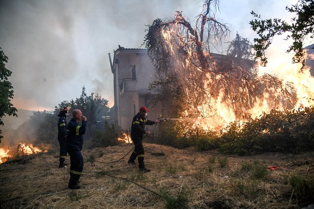 Firefighters try to extinguish a fire burning near a house as a wildfire burns at the village of Kontodespoti, on the island of Evia, Greece on August 13, 2019. (Photo by Michalis Karagiannis/Eurokinissi via Reuters)