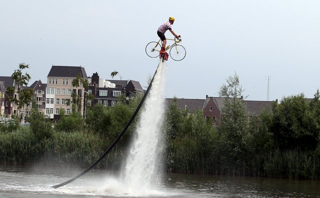 A man wearing a Tour de France best climber's jersey practises flyboarding before the start of the 166-km (103.15 miles) second stage of the 102nd Tour de France cycling race from Utrecht to Zeeland July 5, 2015. (Photo by Stefano Rellandini/Reuters)