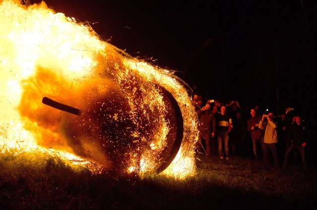 An oak wheel stuffed with straw is set on fire and rolled down a hill to celebrate the Easter Wheel (Osterraeder) tradition in Luedge, Germany, 20 April 2014. Originally a custom of a sun cult by which the awaking spring was welcomed, the rolling of burning wheels has taken place on Easter Sunday for centuries. The custom is in the finals for the German application for the inclusion of cultural customs in the Unesco Intangible cultural heritage list. (Photo by Caroline Seidel/EPA)