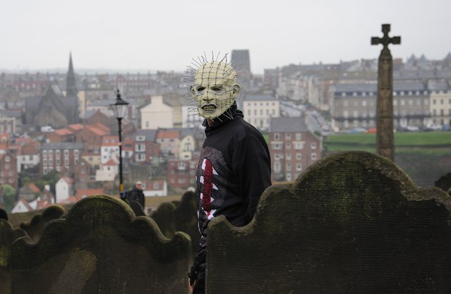A man wearing a 'Pinhead' mask walks through the grounds of St Mary's Church, Whitby, during the Whitby Gothic festival taking place this weekend, on  April 27, 2014. The twice yearly event attracts Goths from across the UK and beyond to the historic fishing town and is a great boost to the local economy. (Photo by Anna Gowthorpe/PA Wire)