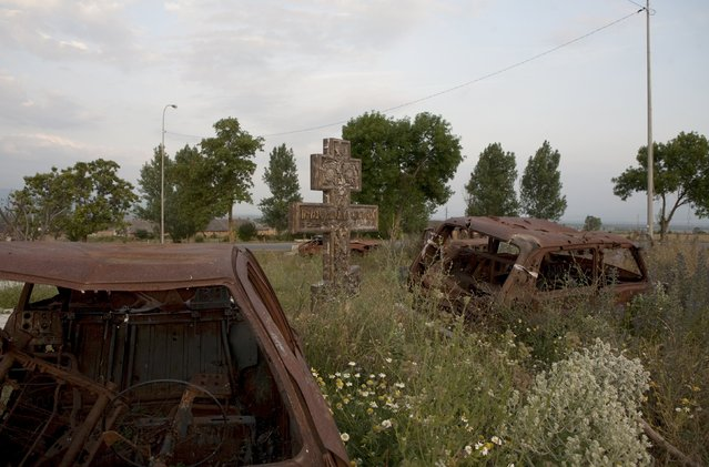 Abandoned cars are seen around a cross in the village of Tbeti near Tskhinvali, the capital of the breakaway region of South Ossetia, Georgia, July 4, 2015. President Vladimir Putin signed a treaty with Georgia's rebel South Ossetia region on March 18 that almost completely integrates it with Russia, alarming Georgia and the West a year after Moscow took over Crimea. (Photo by Kazbek Basaev/Reuters)