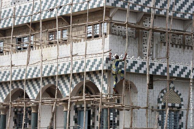 A man climbs the scaffold of a new Mosque, under construction in Ganvie, near Cotonou, Benin