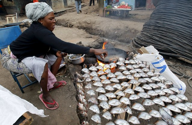 A woman fries fish for sale at her open stall within Mathare valley slums in Kenya's capital Nairobi, July 9, 2015. (Photo by Thomas Mukoya/Reuters)