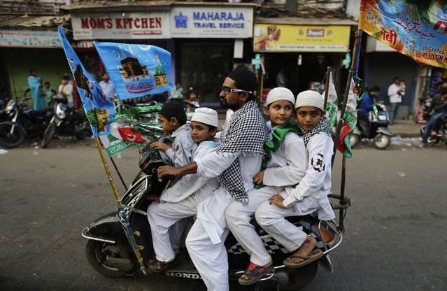 Muslims ride on a scooter on their way to participate in a procession to mark Eid-e-Milad-ul-Nabi, or birthday celebrations of Prophet Mohammad in Mumbai January 14, 2014. (Photo by Danish Siddiqui/Reuters)