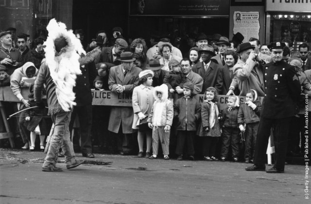 Children watching the Thanksgiving Day Parade in New York as it nears Times Square, 1961