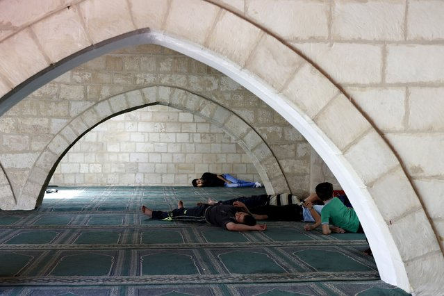 Men rest during the last Friday prayer of the Muslim holy month of Ramadan at al-Husainy mosque in downtown Amman, Jordan, July 10, 2015. (Photo by Muhammad Hamed/Reuters)