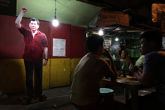 A life-size cut-out of President-elect Rodrigo Duterte looms over diners at a street stall in the center of Davao, Philippines May 13, 2016. (Photo by Andrew RC Marshall/Reuters)