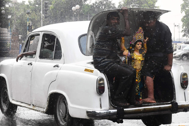 Hindu devotees sit in the boot of a Hindustan Ambassador car with an idol of the Hindu deity Vishwakarma as they transport it in the rain for an immersion ceremony in Kolkata on September 20, 2019. (Photo by Dibyangshu Sarkar/AFP Photo)
