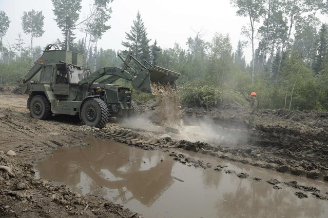 Corporal Dustin Zsovak, 1 Combat Engineer Regiment guides Corporal Willis Johnson who operates a multi-purpose engineering vehicle to clear a road near La Ronge, Saskatchewan July 10, 2015 in a picture released by the Canadian Armed Forces. The Canadian military has been called in to help fight wildfires in the Western province of Saskatchewan, where over 100 active fires have forced the evacuation of more than 13,000 people and threatened several remote towns. (Photo by MCpl Melanie Ferguson/Reuters/Canadian Forces)
