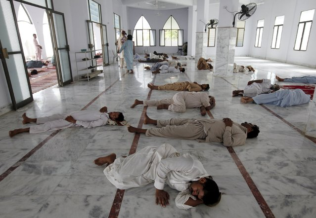 Men sleep on the floor during a heat wave, at a mosque at the premises of Jinnah Postgraduate Medical Centre (JPMC) in Karachi, Pakistan, June 28, 2015. (Photo by Akhtar Soomro/Reuters)