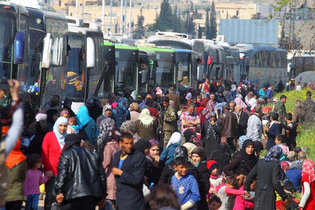 People that were evacuated from the two villages of Kefraya and al-Foua walk near buses, after a stall in an agreement between rebels and Syria's army, at insurgent-held al-Rashideen, Aleppo province, Syria April 15, 2017. (Photo by Ammar Abdullah/Reuters)
