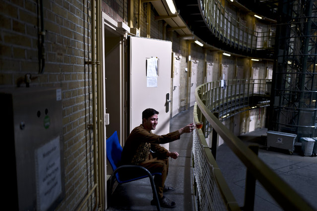 In this Sunday, May 1, 2016 photo, Afghan refugee Siratullah Hayatullah, 23, drinks tea by the doorway of his room at the former prison of De Koepel in Haarlem, Netherlands. (Photo by Muhammed Muheisen/AP Photo)