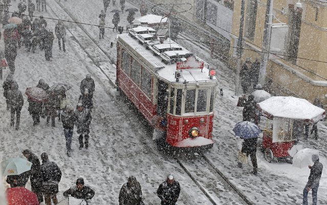 People brave the cold and snow as they walk in the main pedestrian street of Istiklal in central Istanbul, in this February 17, 2015 file photo. (Photo by Murad Sezer/Reuters)