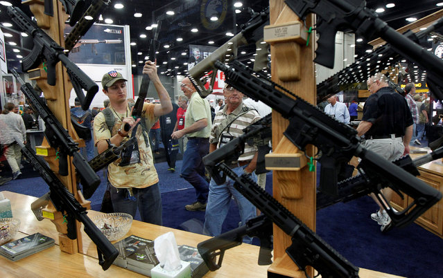 Gun enthusiasts look over Rock River Arms' guns at the National Rifle Association's annual meetings and exhibits show in Louisville, Kentucky, May 21, 2016. (Photo by John Sommers II/Reuters)