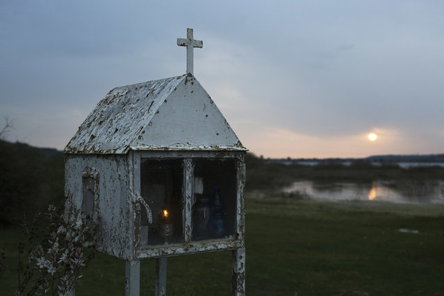 In this photo taken on Saturday, April 29, 2017, a candle is lit in a roadside shrine as the sun sets across a nearby lake of Pineia in the village of Souli, in the Peloponnese region of southern Greece. (Photo by Petros Giannakouris/AP Photo)