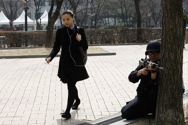 A woman walk by South Korean police during a anti-terror exercise