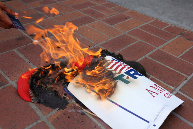 Anti-Trump demonstrators burn Donald Trump's campaign items outside a campaign event for Republican U.S. presidential candidate Donald Trump in San Diego, California, U.S. May 27, 2016. (Photo by David McNew/Reuters)