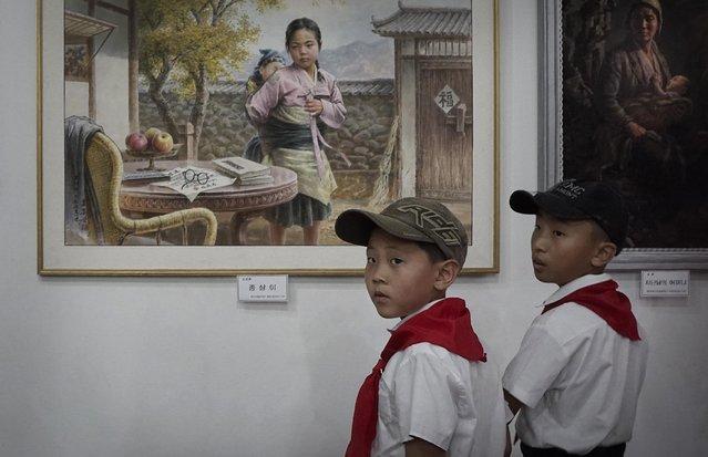 North Korean school boys look at paintings on display, Sunday, July 26, 2015, in Pyongyang, North Korea. (Photo by Wong Maye-E/AP Photo)