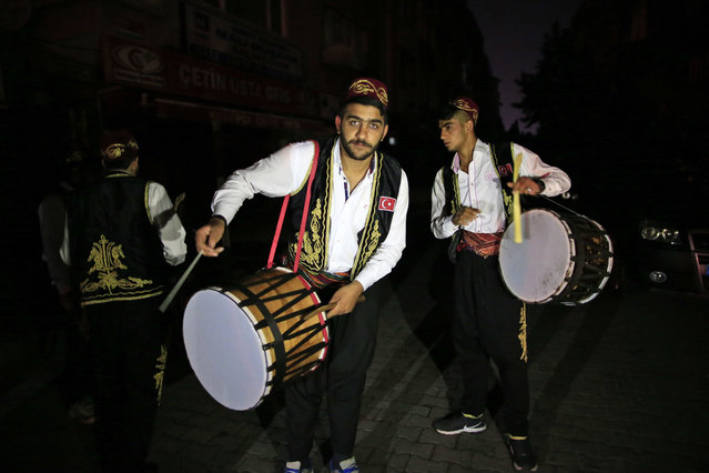 """On the first day of the Muslim holy month of Ramadan, drummers, wearing traditional Ottoman clothes, perform through the neighborhoods of Istanbul, early Monday June 6, 2016 to wake people for the """"sahour"""", the traditional breakfast of Ramadan. More than 2000 drummers wander Istanbul's neighborhoods playing their drums in the early hours to wake up the residents as part of the holiday tradition. (Photo by Lefteris Pitarakis/AP Photo)"""