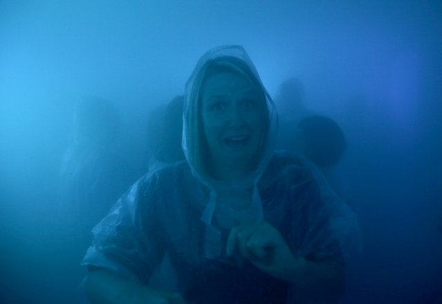 A woman partygoer reacts at the Bompas and Parr's Architecture Bar in London, Britain, July 31, 2015.  Visitors to the bar, dressed in protective ponchos, walk into a breathable cocktail cloud composed of spirits and mixer at a ratio of 1:3. (Photo by Peter Nicholls/Reuters)