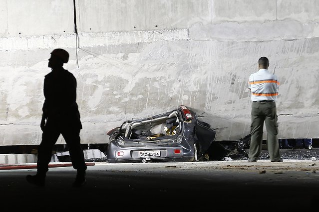 A car is trapped underneath a bridge that collapsed while under construction in Belo Horizonte July 3, 2014. The unfinished overpass collapsed in the Brazilian World Cup host city of Belo Horizonte on Thursday, killing at least one person and casting a shadow over a tournament that has suffered repeated construction accidents and delays. (Photo by Ivan Alvarado/Reuters)