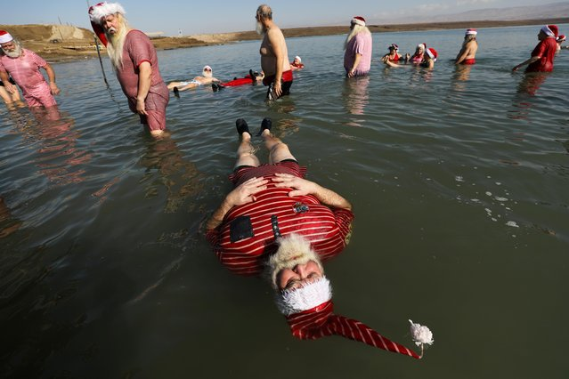 A man, part of a group of trained Santa Clauses from various countries, wears a Santa Claus-themed bathing suit as he floats in the Dead Sea, at Neve Midbar beach in the Israeli-occupied West Bank on January 7, 2020. (Photo by Ammar Awad/Reuters)