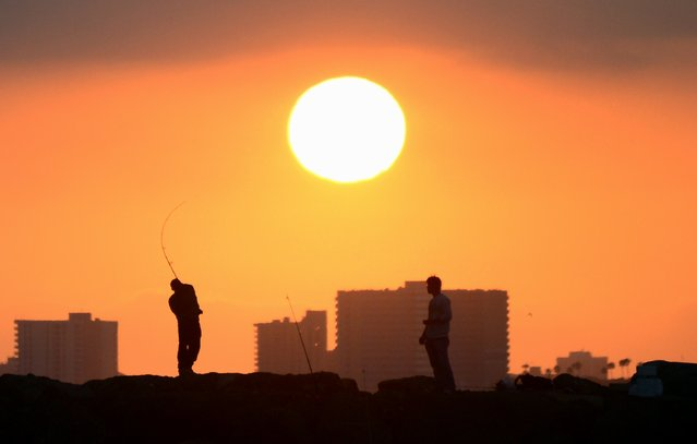 "A fisherman casts his line from the rocks at Seal Beach, California, as the sun prepares to set on June 28, 2014. Summer in California this year is expected to be the hottest and driest on record as nearly one-third of the state experiences ""exceptional"" drought levels, the highest percentage ever recorded by the Drought Monitor, whch began monitoring in 2000, according to reports last week from the National Climatic Data Center. (Photo by Frederic J. Brown/AFP Photo)"