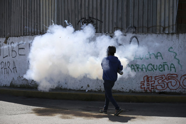 A demonstrator fires fireworks at security forces with a home made mortar during clashes in Caracas, Venezuela, Tuesday, July 4, 2017. Opposition protests demanding new elections and decrying triple-digit inflation, food shortages and worsening crime continue as President Nicolas Maduro pushes forward with his plan to draft a new constitution. (Photo by Fernando Llano/AP Photo)