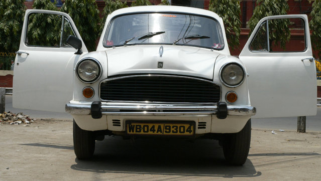 A driver, unseen, takes rest inside an Ambassador car in Calcutta, India, Wednesday, May 2, 2007. Striking workers have forced India's Hindustan Motors to temporarily shutter the factory that produces the Ambassador, an icon of the Indian roads. (Photo by Bikas Das/AP Photo)