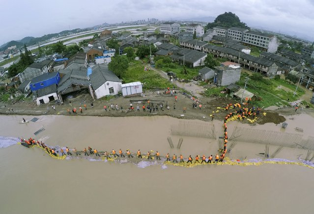 An aerial view shows People's Liberation Army (PLA) soldiers and local residents placing sand bags to block floodwater after a dam breached under the influence of Typhoon Soudelor, in Pingyang county, Zhejiang province, China, August 9, 2015. Typhoon Soudelor battered China's east coast on Sunday, killing 14 people and forcing the authorities to evacuate hundreds of thousands more. (Photo by Reuters/China Daily)