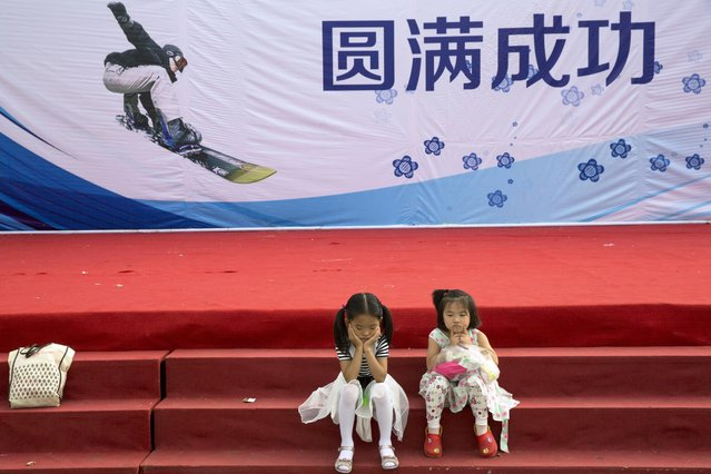 """Chinese girls sit near a backdrop stating """"A Complete Success"""" in honor of  Beijing hosting the 2022 Winter Olympics Saturday, August 1, 2015. Having made history as the first city to win hosting rights for both the Summer and Winter Olympics, Beijing now faces a slew of challenges, from ensuring adequate snow in a bone-dry region to ramping up support for winter sports in a nation where few people ski or skate. (Photo by Ng Han Guan/AP Photo)"""