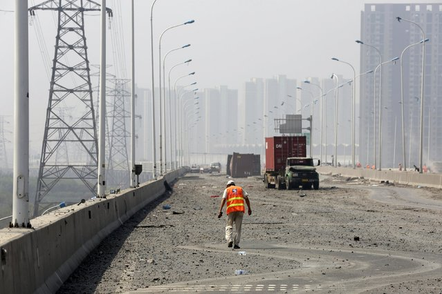 A worker cleans a highway near the site of the explosions at the Binhai new district, Tianjin, August 13, 2015. (Photo by Jason Lee/Reuters)