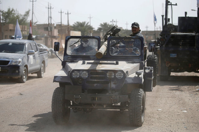 Iraqi security forces ride in a military vehicle in Falluja, Iraq, June 25, 2016. (Photo by Thaier Al-Sudani/Reuters)