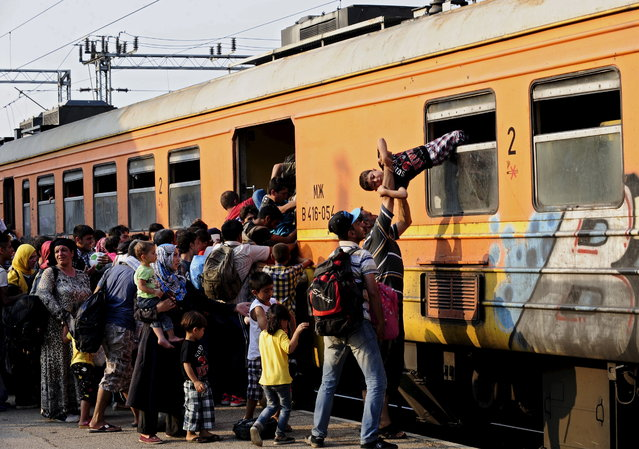 Migrants clamber onto a train at Gevgelija train station in Macedonia, close to the border with Greece July 30, 2015. (Photo by Ognen Teofilovski/Reuters)