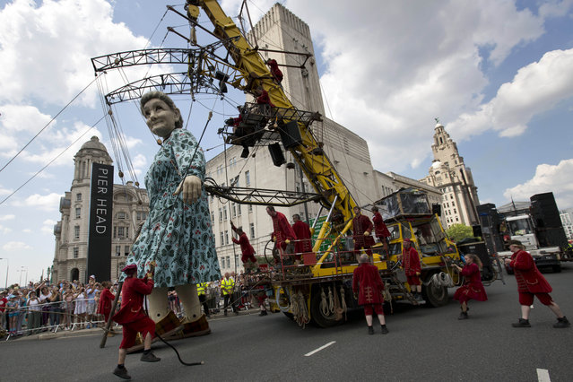 A grandmother giant marionette passes the Pier Head in the centre of Liverpool as she and two other giant marionettes, a girl and a dog, parade through the streets, in Liverpool, England, Friday, July 25, 2014. The huge figures begin the three-day commemoration of World War One. Royal de Luxe, the French street theatre company organised the event. (Photo by Jon Super/AP Photo)