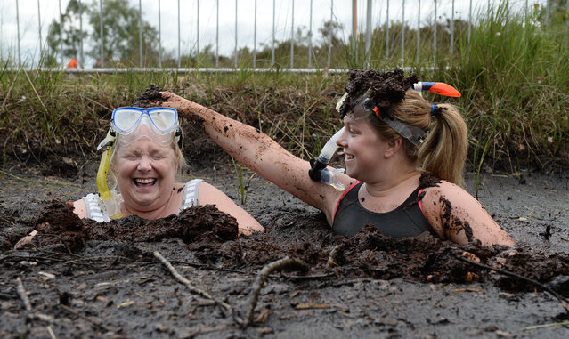 Two female entrants take a dip in the Bog Jacuzzi after takes part in the Irish Bog Snorkelling championship this afternoon at Peatlands Park on July 27, 2014 in Dungannon, Northern Ireland. The annual event sees male and female competitors swim the 60m length of the bog watched by scores of spectators and takes place on International Bog Day. (Photo by Charles McQuillan/Getty Images)
