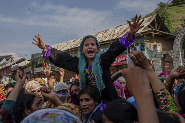 A Kashmiri village girl shouts pro-freedom slogans during the funeral procession of a civilian Tanveer Ahmed Wani in Beerwah about 40 kilometers (25 miles) west of Srinagar, Indian controlled Kashmir, Friday, July 21, 2017. The Indian army fired at worshippers outside a mosque in disputed Kashmir on Friday, killing one man and injuring another, after some threw rocks, police and residents said. (Photo by Dar Yasin/AP Photo)