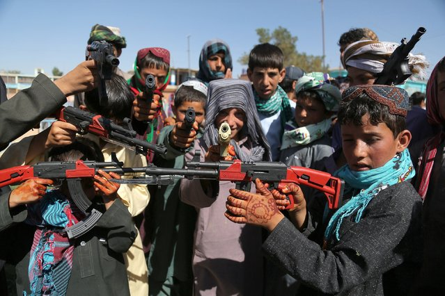 Afghan children play with plastic guns as they celebrate Eid al-Fitr and the end of the fasting month of Ramadan in Ghazni on July 28, 2014. Muslims around the world are celebrating Eid al-Fitr this week, marking the end of the holy month of Ramadan during which followers are required to abstain from food, drink and s*x from dawn to dusk. (Photo by Rahmatullah Alizadah/AFP Photo)