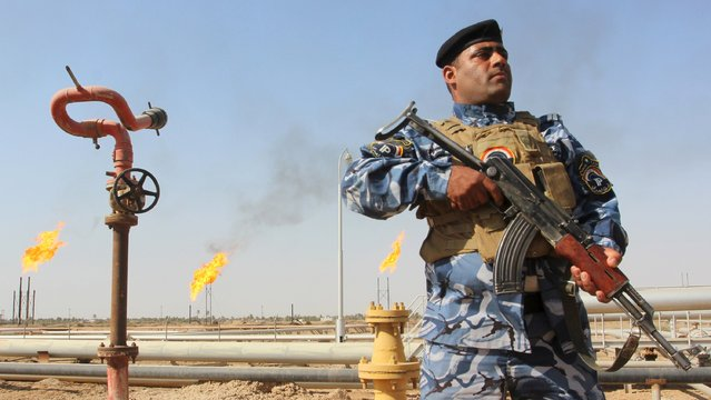 A member of the oil police force stands guard at Nahr Bin Umar oil field, north of Basra, southeast of Baghdad August 19, 2015. Iraq's oil exports have fallen by at least 250,000 barrels per day (bpd) so far in August according to loading data, making it less likely the several-month trend of rising OPEC output that has weakened oil prices will be sustained this month. (Photo by Essam Al-Sudani/Reuters)